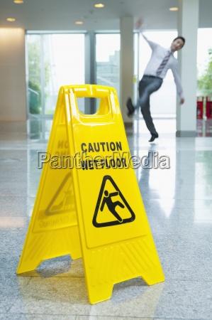 businessman slipping behind wet floor sign