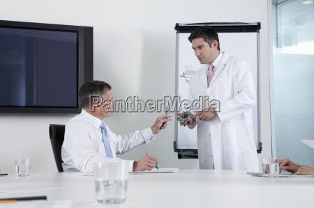 engineer showing businessman machine part in