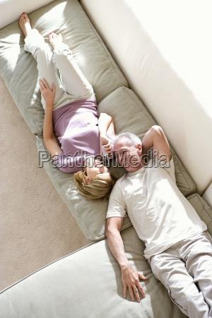 senior couple lying at opposite ends
