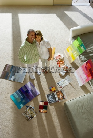 senior couple standing beside colour charts