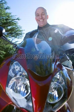 senior man sitting on red motorbike