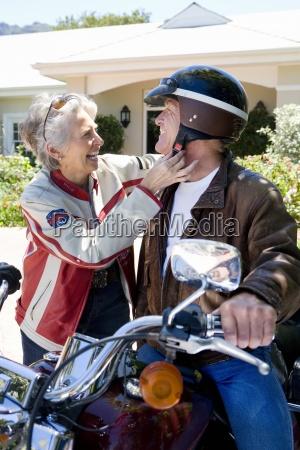 senior man sitting on motorbike on