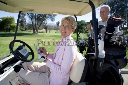 mature couple playing golf woman sitting