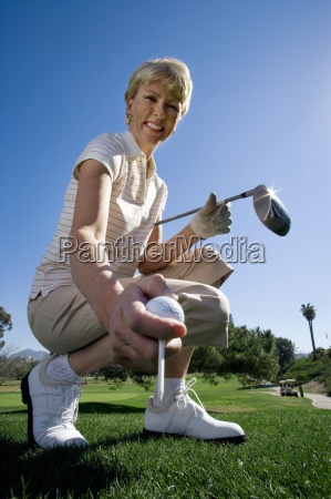 mature woman placing golf tee on