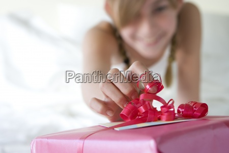 girl 11 13 touching red ribbon
