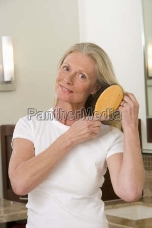 senior woman brushing long straight hair