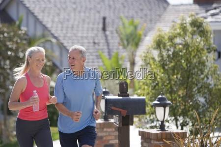 active senior couple in sportswear jogging
