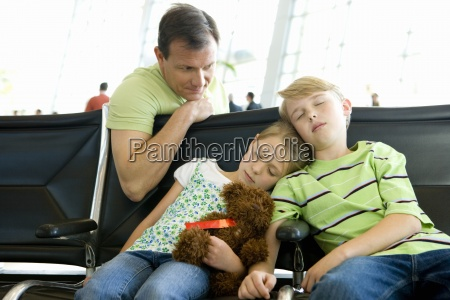father looking at children sleeping on