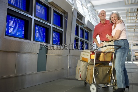 senior couple standing with luggage trolley