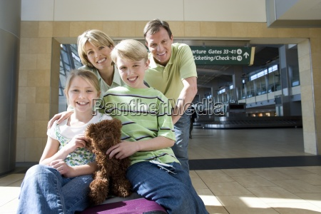 family standing beside luggage trolley in