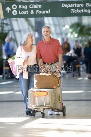 senior couple pushing luggage trolley below