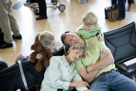 family waiting in airport departure lounge