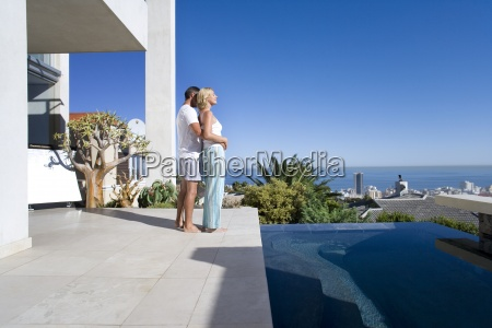 couple embracing on balcony by swimming