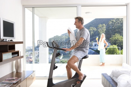 mature man riding stationary bicycle in
