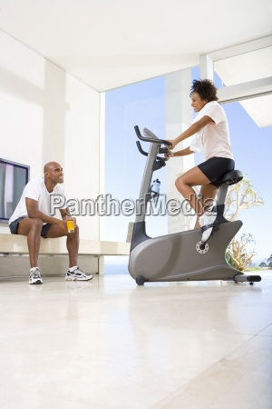 woman on stationary bicycle by man