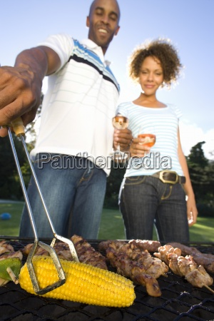 couple having barbeque outdoors standing by