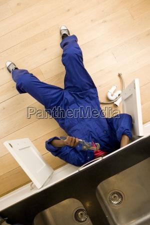 plumber working under kitchen sink overhead