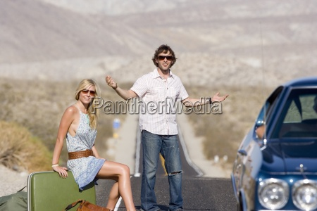 young couple hitchhiking on desert road