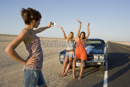 young woman taking photograph of friends