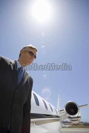businessman by aeroplane on runway low