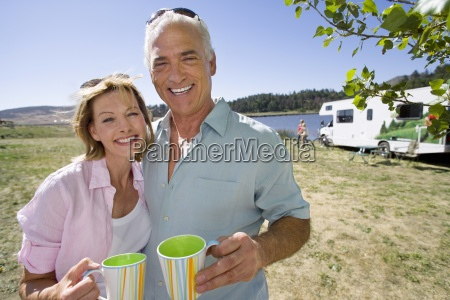 mature couple with mugs by motor