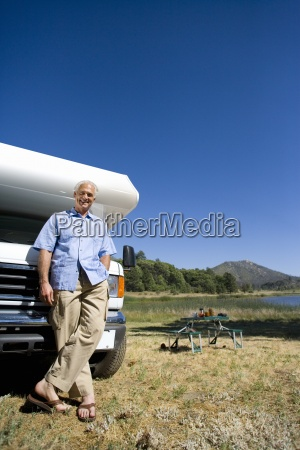 mature man by motor home and