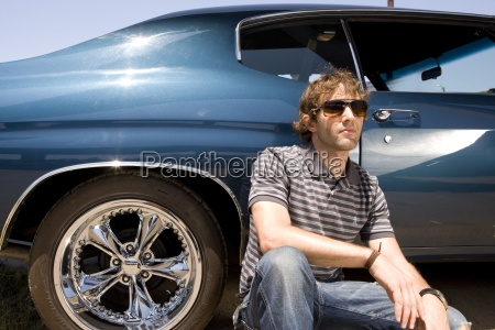 young man in sunglasses by car