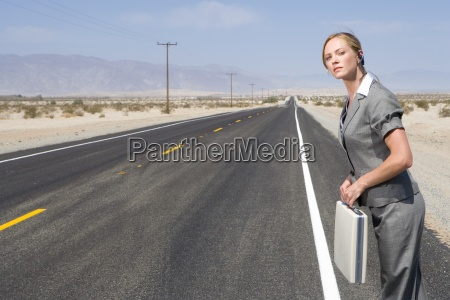 businesswoman on side of road in