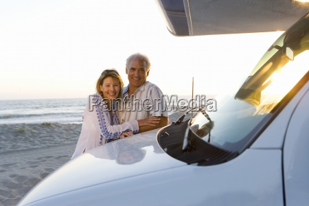 mature couple embracing by motor home