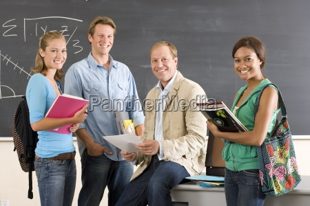 male teacher sitting on desk in