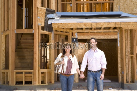 young couple holding hands on building
