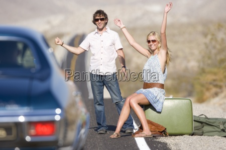 young, couple, hitchhiking, on, desert, road, - 12935536