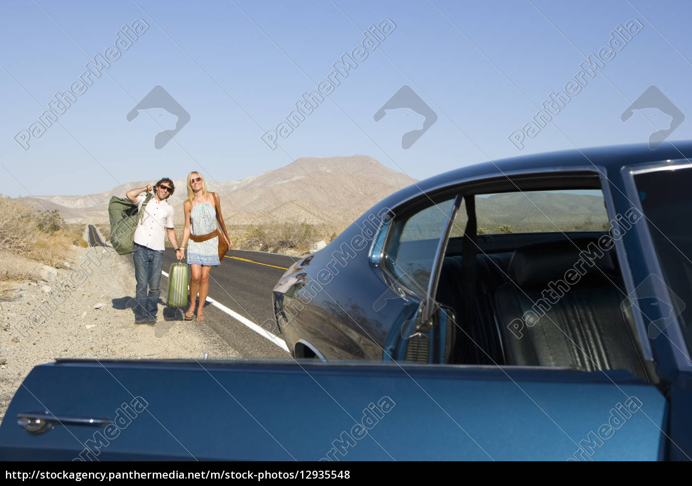 young, couple, hitchhiking, on, desert, road, - 12935548