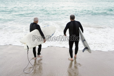 male surfers in wetsuits on beach