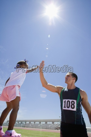 male athlete giving girl 3 5