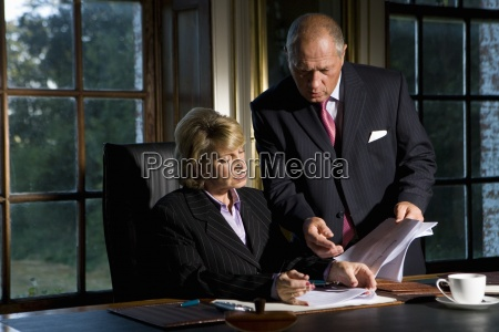businessman showing paperwork to businesswoman at