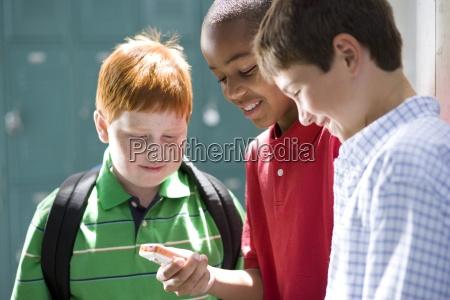 boy 10 12 showing friends mobile