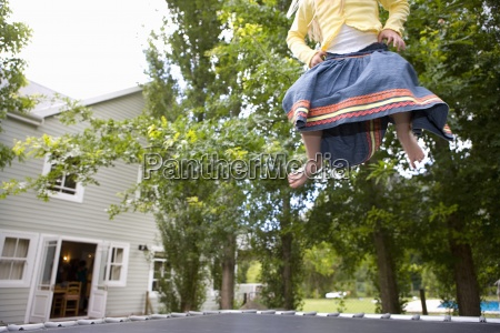 girl 9 11 playing on trampoline