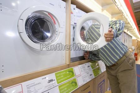 man shopping head in washing machine