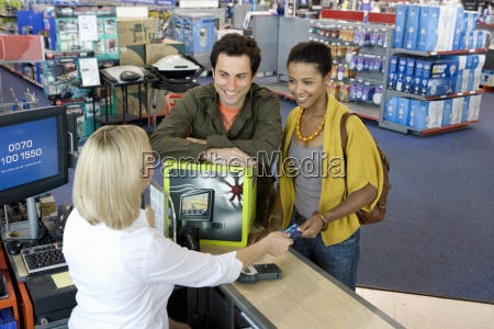young couple buying computer smiling elevated