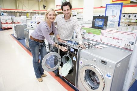 young couple shopping for washing machine