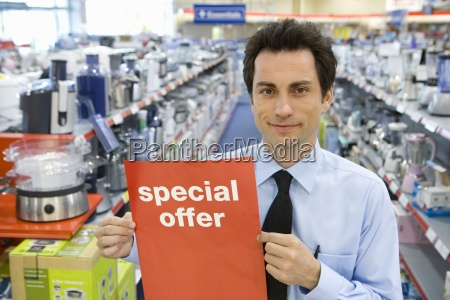 young salesman with special offer sign