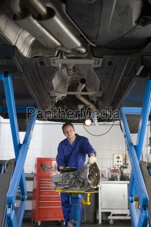 mechanic with part by elevated car
