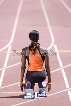 african female runner at starting block
