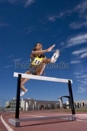 african female runner clearing hurdle