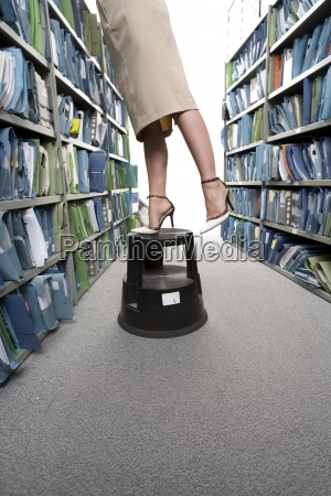 businesswoman on stool reaching for file