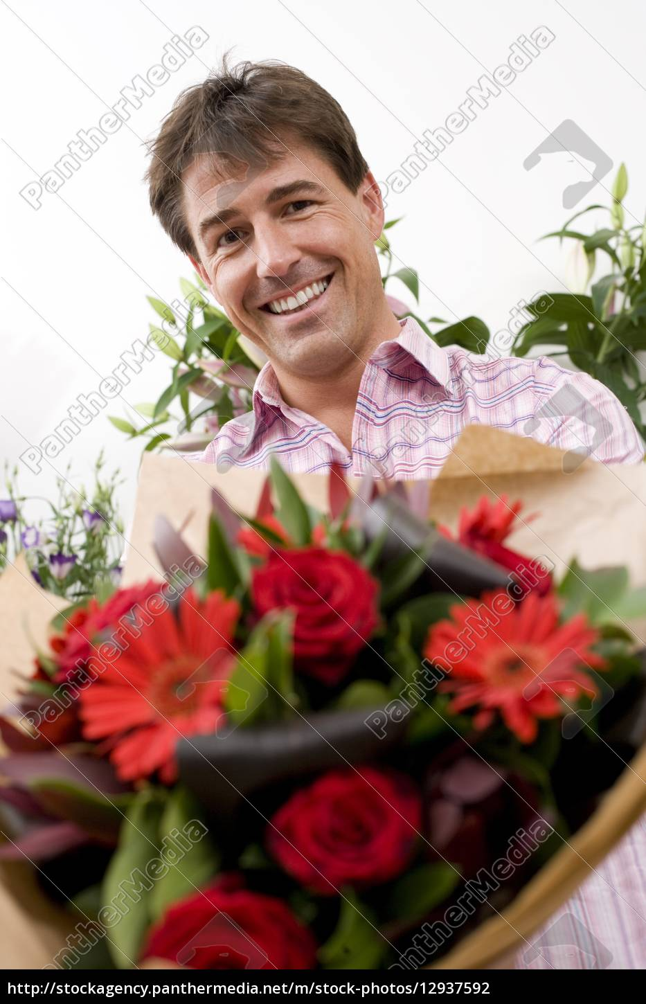 Man with bouquet of flowers smiling portrait low royalty free royalty free photo 12937592 man with bouquet of flowers smiling portrait low angle view izmirmasajfo
