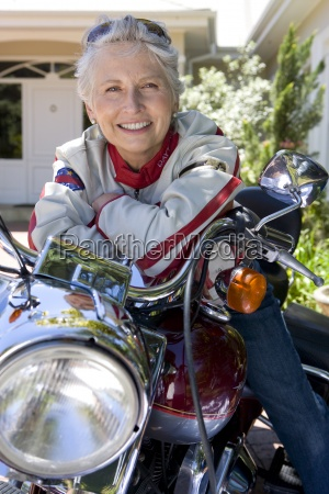 senior woman posing on motorcycle