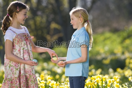 two young girls holding decorated easter