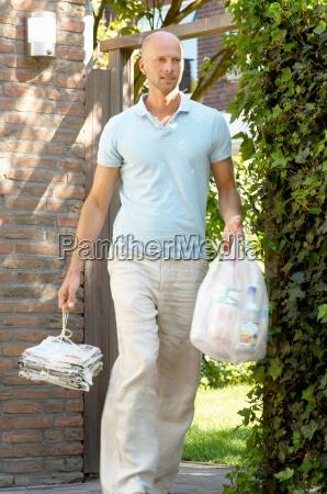 mature man carrying garbage bags den